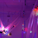 A pink, red, and purple-lit installation shot of ethereal, motorized sculptural works by Shih Chieh Huang.