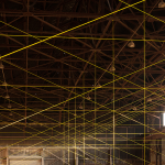 Image: Photograph of a site-specific installation in a building's interior, made of yellow rope, beam clamps, and eye bolts.