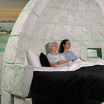 Image of two women laying down on a bed that is shaped like an iglu.