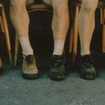 Color photograph focusing on five pairs of legs and feet sitting side by side, each pair wears mismatched shoes.
