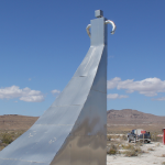 Metallic tall structure in desert landscape and blue sky by Zaq Landsberg