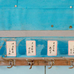 Color image of horizontal coat hanger over blue wall; above each hook are faded labels with Japanese characters.