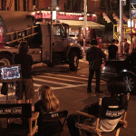 Image of film crew on the street at night, nine individuals have their backs to the camera, five of hem are sitting down, facing a truck.