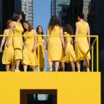 Image: A group of seven women in yellow dresses stand on an elevated yellow box-structure with a yellow railing.