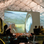 Image: People sit on top of wrecked cars in an indoor drive-in movie setting.