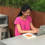 Image: A woman sits upright at her laptop computer in an outdoor setting.