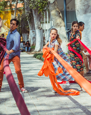 Image: Three dancers pull on brightly-colored fabric strips on the sidewalk in an urban setting.