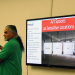 "Picture of Ravi Agbir in front of a screen that reads ""Art Spaces as Sensitive Locations"""