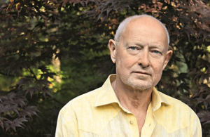 Image: a headshot of Michael Findlay, a distinguished man with white hair wearing a casual yellow button down shirt who stands in front of a maple tree.