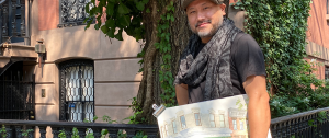 "Photograph of Kazuya ""Kaz"" Morimoto holding a painting and standing in front of a brownstone"