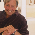 Image: A man, Robert Rauschenberg, is sitting in a white gallery-like setting in front of his own artworks. His hands are clasped together as he smiles into the camera.
