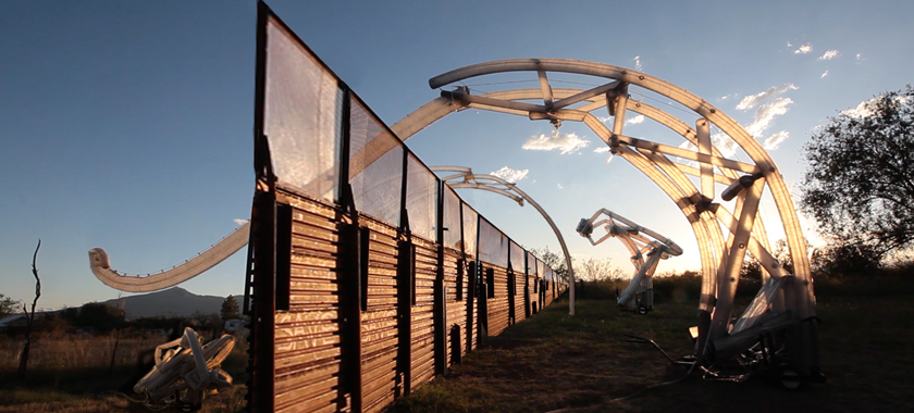 Image: This composite image displays the vision of MacMurtrie's ongoing Border Crossers project: Six inflatable robotic sculptures rise up to several stories high and extend across the U.S.-Mexico border. The Border Crossers are depicted in different stages of activation: deflated, activated, and fully deployed over the border fence.