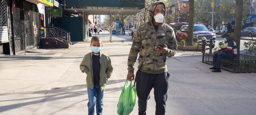 Image: A man wearing a camouflage hoodie, athletic pants, and a mask carries a green plastic shopping bag and cell phone while walking on a New York City sidewalk in Harlem. His son walks beside him, also wearing a mask.