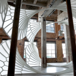 Image: A light, airy, cathedral-like structure installed in a tall industrial space.