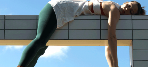 Photo of an individual in green tights and white shirt laying over a tiled structure