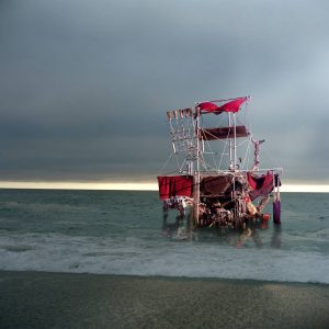 Photograph of mixed media sculpture that resembles a red raft on the sea and overcast skies