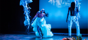 Image: Cropped photograph of a blue-lit dance performance. Two dancers, a woman and a man, appear on stage with jellyfish dangling from above. They are caught mid-movement against a screen with a seashell on it.