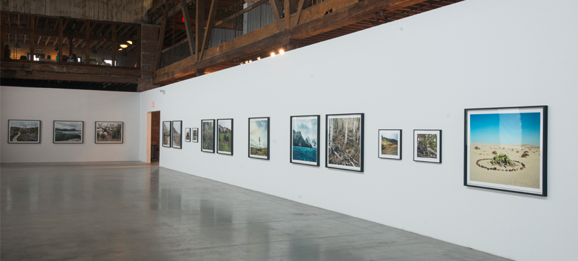 Image: A white wall is built out in a large industrial space with giant wood beams and a concrete floor. An exhibition of photographs is hung on the wall in the space.
