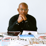 Headshot of Amani Olu with several publications on a table
