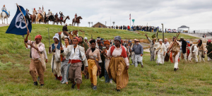 Image: A group of Black reenactors are pictured walking on grass and along a highway. They wear period dress from the early 1800s and carry weapons; some on higher ground are on horseback. A man in front carries a blue flag with a white emblem on it.