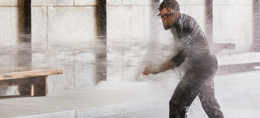 Image: a man (Dread Scott) wearing all black with black glasses attempts to walk forward while repeatedly battered and occasionally knocked down by a water jet from a fire hose.