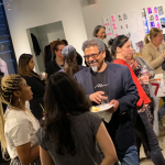 Image: A social gathering of artists participating in NYFA's Immigrant Artist Mentoring Program: Newark. It appears to be a mixer event, as people mingle in a large, gallery-like setting and hold drinks and plates of food.