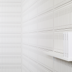 Image of two walls meeting at the corner of a room, which is covered in a wallpaper that shows symmetrically spaced columns, where the black outlines of 20 volumes of Print Wikipedia editions are lined up as if they were all placed on a shelf.