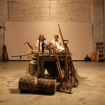 Young men and women sit very still inside a raw building, sitting left and right of a large, central wooden table that is covered with old farming utensils and tools.
