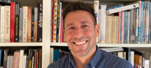 Image: A man smiles broadly into the camera, pictured from the shoulders up against what bookshelves. He wears a blue button-down shirt with small white dot print and has dark hair.