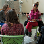 Six individuals sitting on green chairs hold a conversation