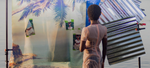 Image Detail: A color photograph of a figure standing in a body of water at sunset. She is facing away from the camera. There is a photographic backdrop in the water behind her decorated with a fabric with a photo a palm tree on it, as well as pieces of corrugated steel.