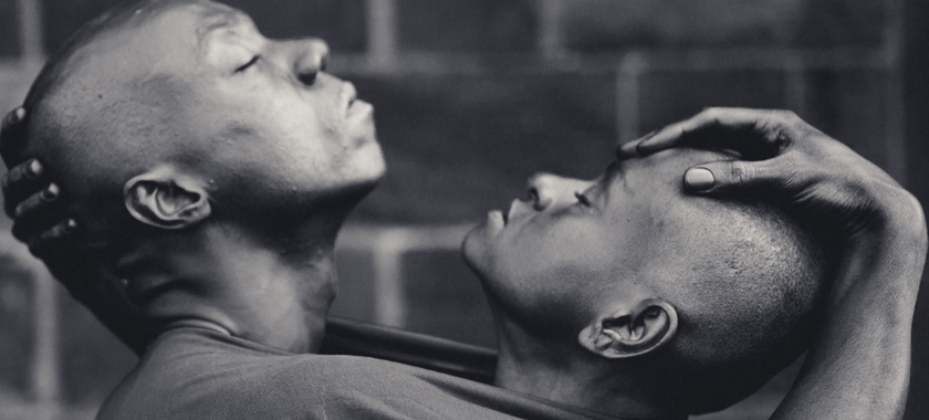 """Image Detail: This photo of """"BLACK VELVET"""" was taken at Governor's Island, NYC in 2018 by photographer Alex Apt. The subjects are performers Mirelle Martins and Shamel Pitts. The moment captured symbolizes the soothing embrace of one's other half as a reflection of self."""