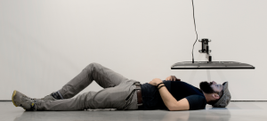 Image: Monitor installed in a gallery-like setting in an atypical spot with the screen facing the ground, only a few feet from the ground. A man lays on the floor, face up towards the screen.