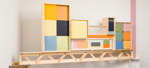 Image: Sculpture by Jim Osman that was installed in the corner of a gallery space using an existing beam post. It spans the space with a wood truss that attached to a beam that is painted pink; the other end rested on a pseudo cabinet. Colorful boxes were arranged on top.