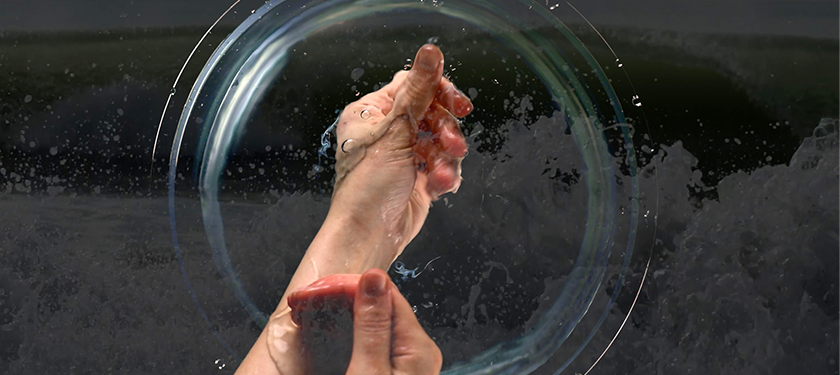 Image of two hands being submerged in a transparent liquid