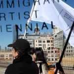 """Image: A small group of artists walk together over the Brooklyn Bridge with city buildings in the background. They carry a white flag with black text that reads: """"Immigrant Artist Biennial."""" There is a """"watermark"""" of the Immigrant Artist Biennial logo over the image."""