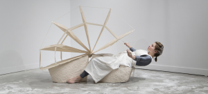 Image: In the center of the photograph is a female performer sitting on a saddle-like ceramic structure. The saddle structure is in the shape of a 2.5' x 26' wedge with another wedge mirroring it. We are viewing her profile. Her body position suggests movement forwards and backward while in each outstretched hands she grasps cotton twill tape which is attached to 2.5' x 5' teardrop-shaped cloth fan blades anchored into the wedges.