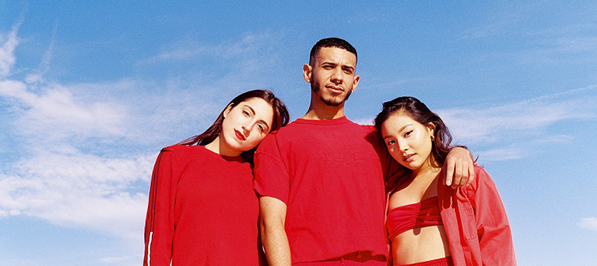 Image of three individuals wearing red clothes against a blue sky