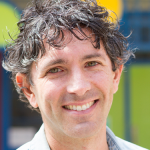 Headshot of David Lavin over a blurred colorful backgrounf