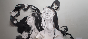 A medium-sized black and white installation with two portraits, one gazing slightly above the viewer and the other looking off into the distance facing the left.