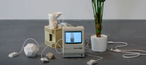Two 1980's era Macintosh computers are surrounded by a plaster cast polyhedron, stones, wires, cast resin Apple mice, a partial 3D print of the bust of Nefertiti, and a plastic plant.