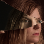 Image Detail: Close-up of a woman's face, which is turned towards the right and obscured by a shard of glass she is holding. The glass reflects a pair of eyes back, presumably the same woman's. She is dramatically lit against a black background.