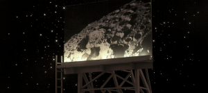 Photograph is of a large billboard, which stands against a starry night sky. On the billboard is an image of a portion of the moon, showing off one of its large craters.