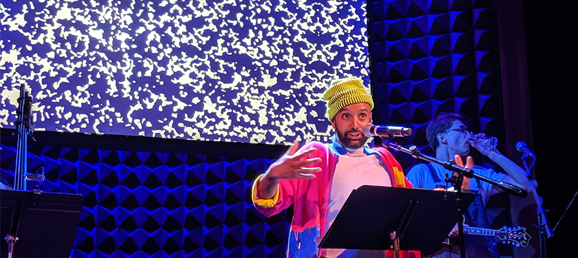 Photo of Shayok Misha Chowdhury wearing a yellow beanie and magenta jacket speaking in front of a blue textured scenery