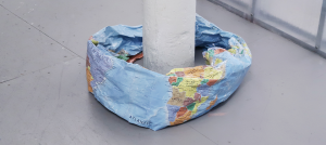 Photo of a wrinkled world map in the shape of a donut around a white pillar