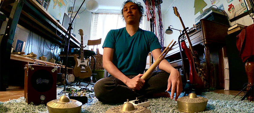 Chaitanya Tamayo poses in a room sitting on a carpet and surrounded by musical instruments