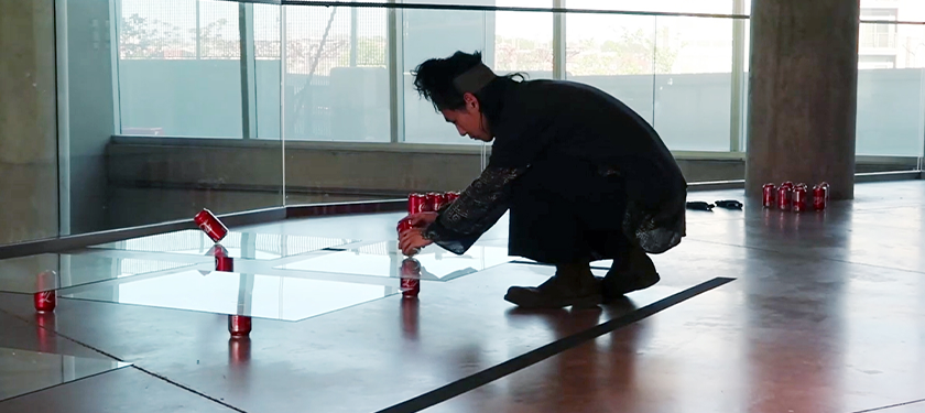 Photo of artist Jaejoon Jang placing cans of Coca-Cola over and under sheets of glass