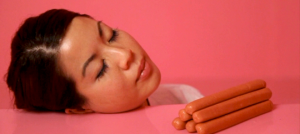 Image of an individual resting her head on a pink table with sausages