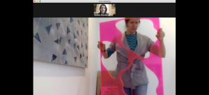 Image: Screen shot from an online studio visit being conducted by Zoom. Artist Ann Tarantino holds a bright pink piece of plastic with boldly-shaped images cut out. There is a large painting behind her on the wall. There is a small thumbnail of Heather Bhandari above.