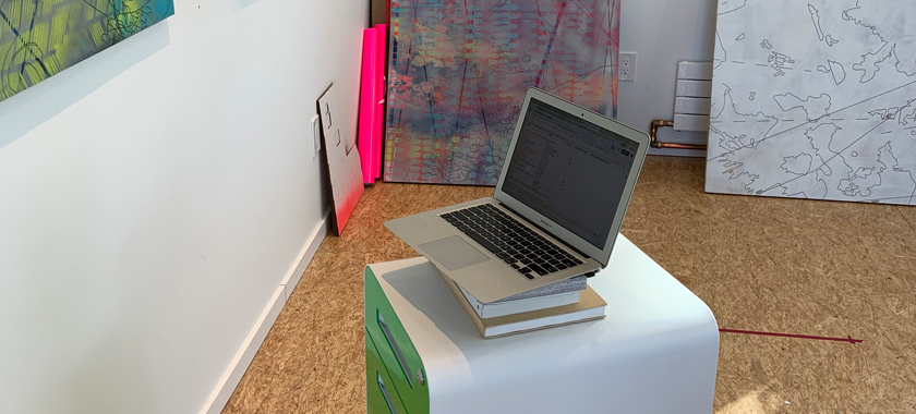 Image: A laptop device sits on a portable file cabinet in artist Ann Tarantino's studio. There is a painting hung on one wall and paintings carefully placed against another.